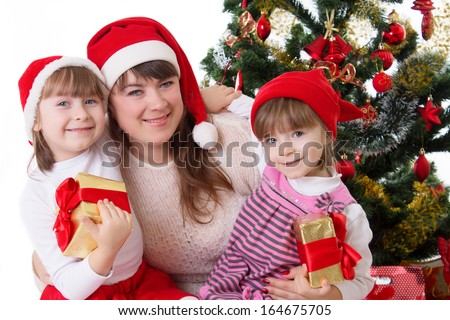 Smiling mother and two daughters under Christmas tree over white