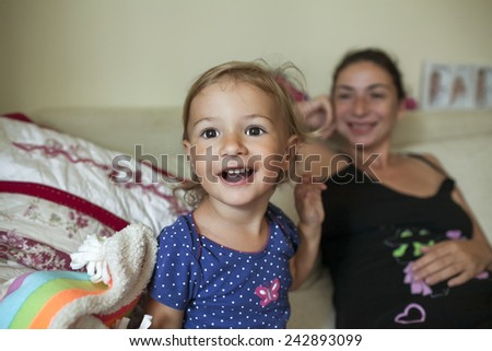 Smiling mother and young child indoors. - stock photo