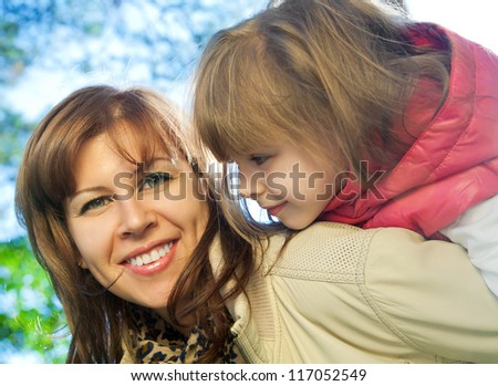 Smiling mother carrying her daughter on back at autumn
