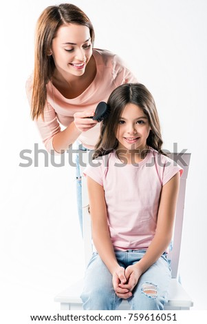 Smiling Mother combing daughters hair isolated on white