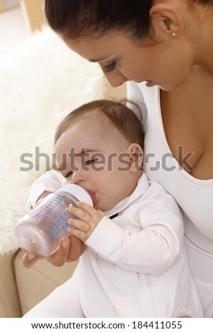 Smiling mother feeding baby boy from feeding bottle. - stock photo