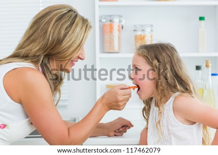 Smiling mother feeding daughter carrot in kitchen