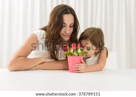 Smiling mother getting flowers from her daughter on mother's Day.Toddler girl giving flowers to her mom on mother's day. Happy family concept - stock photo