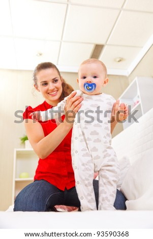 Smiling mother helping baby learn to walk - stock photo