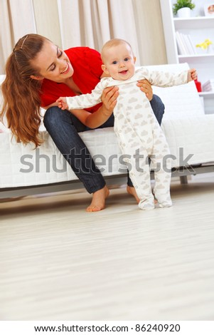 Smiling mother helping cheerful baby learn to walk - stock photo