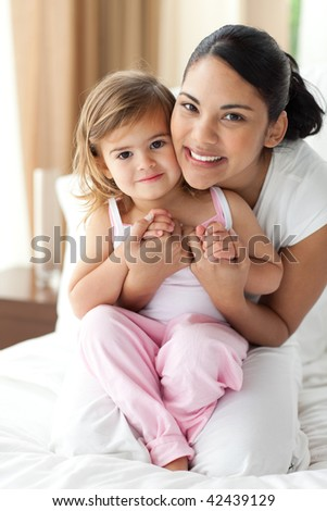 Smiling mother hugging her little girl on the bed