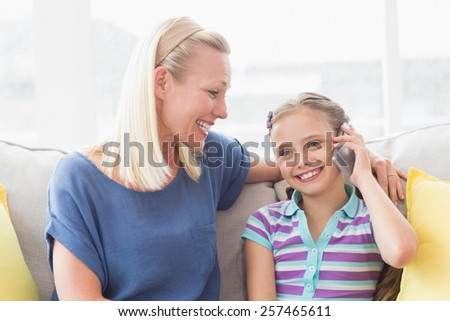 Smiling mother looking at daughter using mobile phone on sofa at home - stock photo