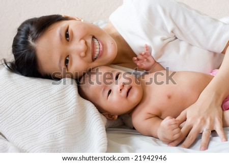 Smiling mother lying in bed with her baby