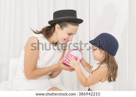 Smiling mother offering her daughter present.Mother giving present to her little beautiful girl. Happy family concept - stock photo