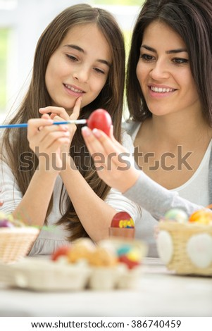 Smiling mother  painting Easter eggs with daughter - stock photo