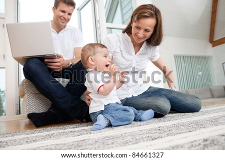 Smiling mother playing with cute child with man using laptop in background