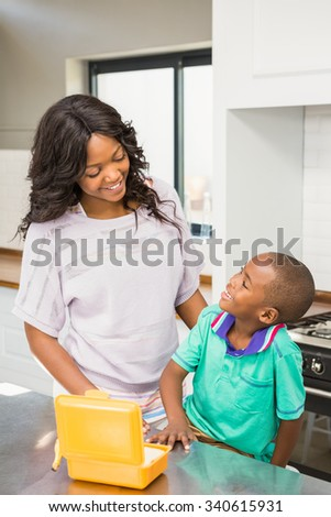 Smiling mother preparing sons school lunch in the kitchen - stock photo