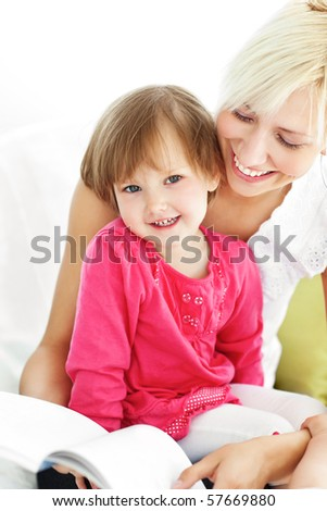 Smiling mother reading a book with children on a sofa - stock photo
