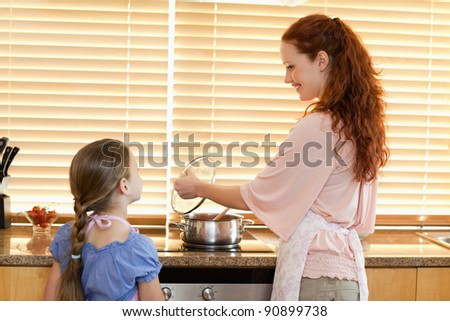 Smiling mother showing her daughter what shes cooking - stock photo