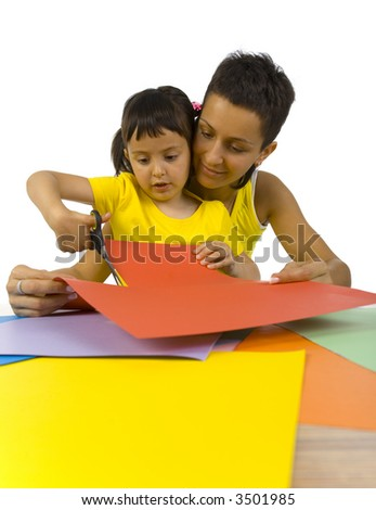 Smiling mother sitting with daughter at desk. Girl cutting paper with scissors. Wide angle, white background - stock photo