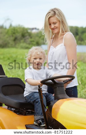 Smiling mother standing near baby boy holding steering wheel