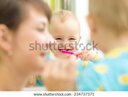 smiling mother teaching kid teeth brushing in bathroom - stock photo