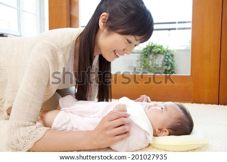 smiling mother watching her baby - stock photo