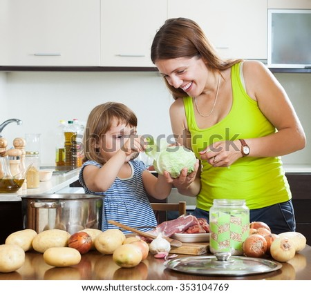 Smiling mother with baby cooking with meat and vegetables - stock photo