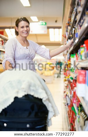Smiling mother with baby stroller in shopping centre looking at camera - stock photo