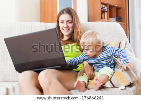 Smiling mother with baby working online with laptop at home