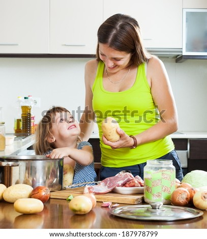 Smiling mother with child cooking with meat and vegetables - stock photo