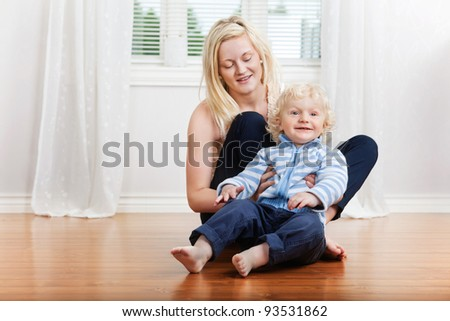 Smiling mother with cute little boy child sitting in house