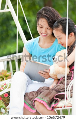 Smiling mother with daughter sitting and looking something on digital tablet - stock photo