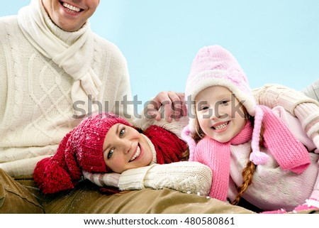 Smiling mother with her daughter lying on their fathers leg and looking at camera