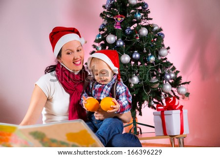 Smiling mother with lovely baby sitting near Christmas tree