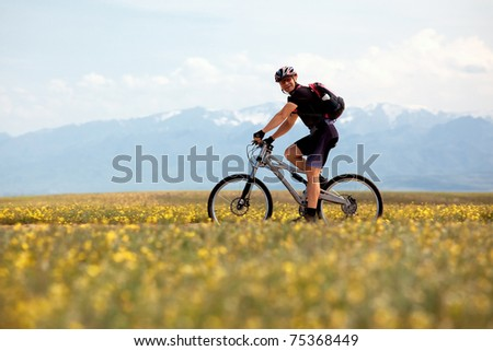 Smiling mountain biker and spring meadow