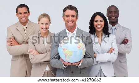 Smiling Multi-ethnic business team holding a terrestrial globe - stock photo