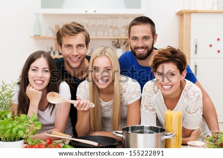 Smiling multicultural group of young men and women cooking in the kitchen posing with their ingredients around the stove - stock photo