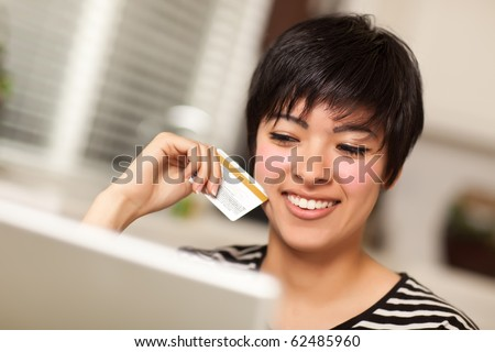 Smiling Multiethnic Woman Holding Credit Card While Using Laptop.