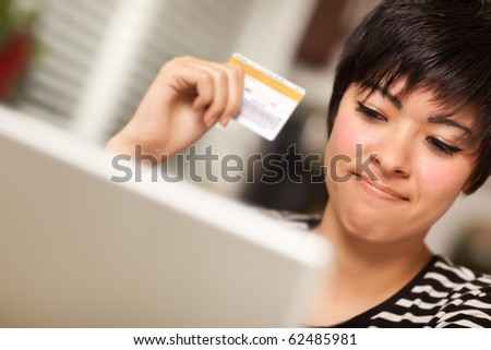 Smiling Multiethnic Woman Holding Credit Card While Using Laptop. - stock photo