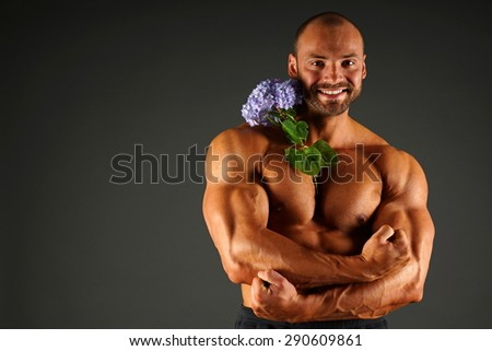 Smiling muscle man poses with beauty blue hydrangea, left you can write some text - stock photo