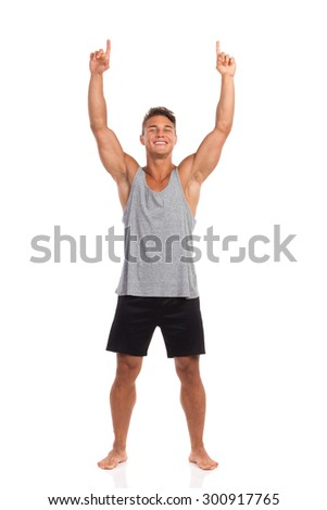 Smiling muscular man standing barefoot with both arms raised and pointing up. Full length studio shot isolated on white.