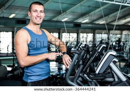 Smiling muscular man using stopwatch at gym - stock photo