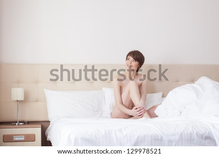 Smiling naked brunette in hotel bed - stock photo