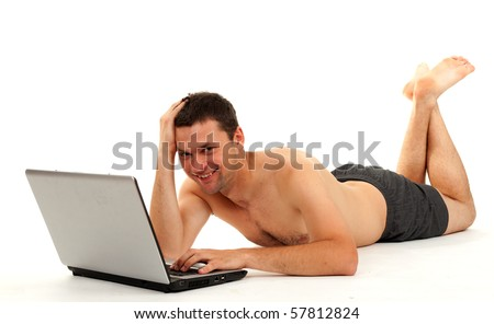 smiling naked man lying on the floor and working on laptop - stock photo