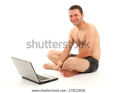 smiling naked man sitting on the floor with crossed legs  and working on laptop - stock photo