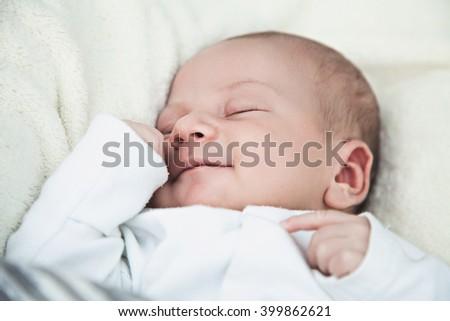 Smiling newborn baby boy asleep - stock photo