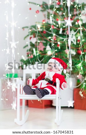 Smiling newborn baby boy in Santa costume sitting in a white rocking chair next to a beautiful Christmas tree - stock photo