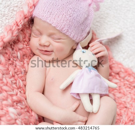 smiling newborn baby girl in a pink hat sleeping with a toy hare