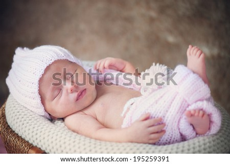 Smiling newborn baby in Hat and Pants on Basket - stock photo