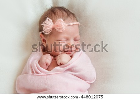 smiling newborn baby sleeping on white blanket - stock photo