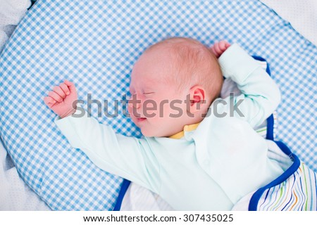 Smiling newborn baby sleeping swaddled in white bed. New born boy taking a nap in blue crib. Kids sleep. Swaddling for infants. Little kid wrapped in warm blanket relaxing in crib with canopy. - stock photo