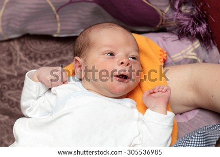 Smiling newborn lying on the bed at home
