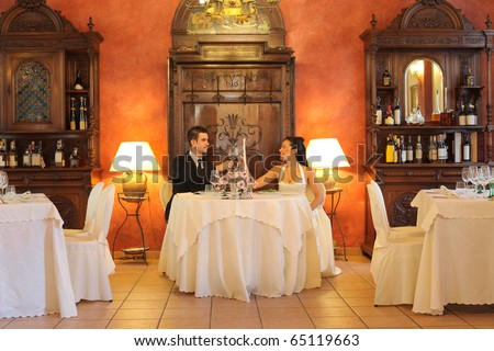 Smiling newlywed couple doing a toast in a luxury restaurant - stock photo