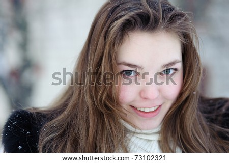 Smiling nice girl against winter background - stock photo